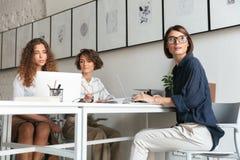 Tre donne graziose che lavorano dalla tavola Fotografie Stock
