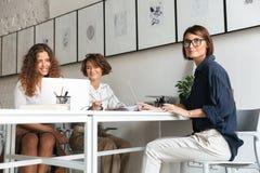 Tre donne graziose che si siedono e che lavorano dalla tavola Immagini Stock Libere da Diritti