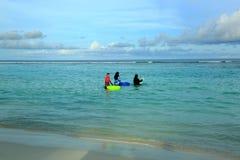 Tre donne musulmane in vestiti variopinti stanno stando nell'acqua e nel nuoto andante Acqua del turchese di Oceano Indiano, Mald fotografia stock libera da diritti