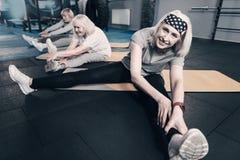 Tre donne senior che eseguono gli allungamenti della gamba Fotografie Stock Libere da Diritti