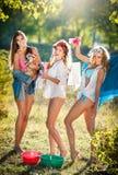 Tre donne sexy con le attrezzature provocatorie che mettono i vestiti per asciugarsi in sole Giovani femmine sensuali che ridono  Immagine Stock