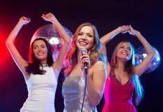 Tre donne sorridenti che ballano e che cantano karaoke Fotografia Stock