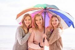 Tre donne sotto l'ombrello variopinto Immagini Stock Libere da Diritti