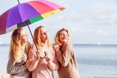 Tre donne sotto l'ombrello variopinto Fotografia Stock Libera da Diritti