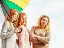 Tre donne sotto l'ombrello variopinto Immagine Stock