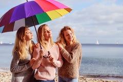 Tre donne sotto l'ombrello variopinto Fotografia Stock