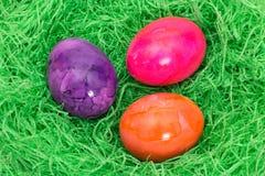 Tre easter ägg i gräset Arkivfoto