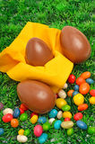 Tre easter chokladägg och caramels på det gröna gräset Arkivbild