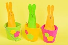 Tre easter kaniner i hinkar på guling Arkivbilder