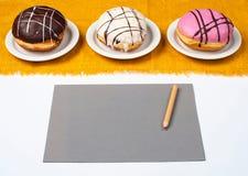 Tre eclairs och papper med en blyertspenna Arkivbilder