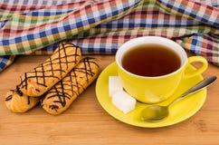 Tre eclairs, varmt te i kopp och socker på tabellen Arkivbilder