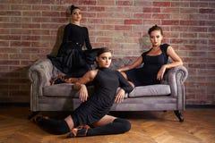 Tre eleganta latinska kvinnadansare i svarta klänningar som poserar nära soffan Royaltyfria Foton