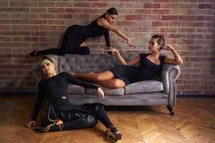 Tre eleganta latinska kvinnadansare i svarta klänningar som poserar nära soffan Royaltyfri Bild