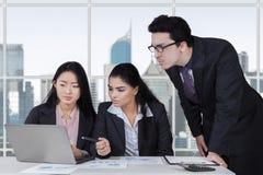 Tre entreprenörer som i regeringsställning planerar ett jobb arkivbild