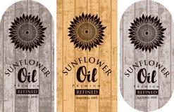 Tre etichette per l'olio di girasole sul contesto di legno Illustrazione di Stock