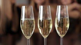 Tre exponeringsglas av champagne på suddig bakgrund stock video