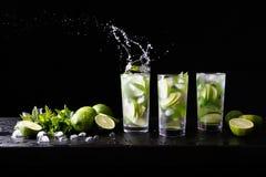 Tre exponeringsglas av förnyelse av coctailen för Mojito romalkohol på stången, färgstänk i ett exponeringsglas Particoctail Lime Royaltyfri Foto