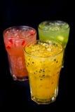 Tre exponeringsglas av fruktfruktsaft på svart bakgrund royaltyfria foton