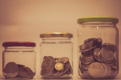 Tre exponeringsglas med ökande mynt som en piggybank arkivbilder