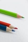 Tre färgade blyertspennor på vit bakgrund Royaltyfri Fotografi