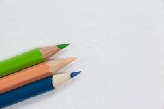 Tre färgade blyertspennor på vit bakgrund Royaltyfria Foton
