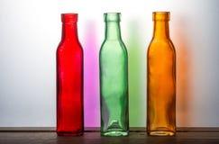 Tre färgade flaskor och deras glass stordia Royaltyfria Foton