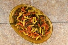 Tre färgade pasta på den glass bunken, bakgrund för keramiska tegelplattor Royaltyfria Foton