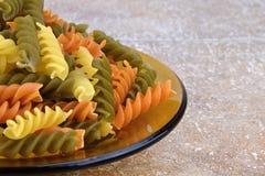 Tre färgade pasta på den glass bunken, keramiska tegelplattor bakgrund, detalj Royaltyfria Bilder