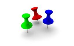 Tre färgglade häftstift i rött, grönt och blått Royaltyfri Bild