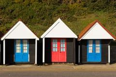 Tre färgglade strandkojor med blåa och röda dörrar i rad Royaltyfria Foton