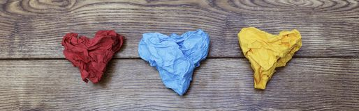 Tre färgrik hjärta formade skrynkliga legitimationshandlingar på trätabellen Valentin` s Dag för vän` s 14th Februari begrepp Arkivbild