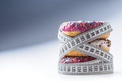 Tre färgrika donuts slåget in i skräddare som mäter bandet Arkivfoton