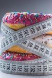 Tre färgrika donuts slåget in i skräddare som mäter bandet Royaltyfri Fotografi