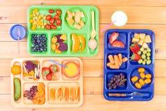 Tre färgrika lunchmagasin på tabellen arkivbild