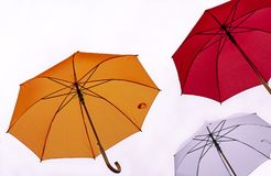 Tre färgrika paraplyer på en vit bakgrund fotografering för bildbyråer