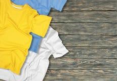 Tre färgrika t-skjortor på träbakgrund arkivbild
