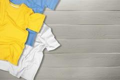 Tre färgrika t-skjortor på träbakgrund arkivfoto