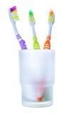 Tre färgrika tandborstar i exponeringsglas Royaltyfri Foto