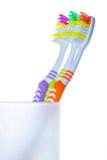 Tre färgrika tandborstar i exponeringsglas Arkivbilder