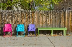 Tre färgrika tomma gräsmattastolar och en bänk Arkivfoton