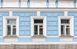 Tre fönster av den gamla 19th århundradeherrgården med blåa väggar royaltyfri fotografi