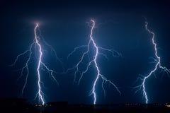 Tre förgrena sig blixtbultar bredvid de slag som är jordnärt från en sträng sommaråskväder i Nederländerna royaltyfria bilder