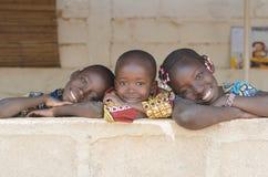 Tre förtjusande afrikanska barn som utomhus poserar kopieringsutrymme Arkivfoton