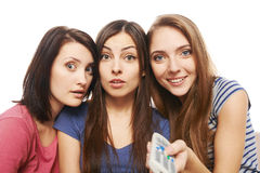 Tre förvånade kvinnor med TVfjärrkontroll Royaltyfri Foto