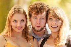 Tre förvånade utomhus- ungdomarvänner Royaltyfri Foto