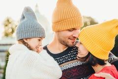 Tre familjemedlemmar står nästan, ser med ögon som är fulla av förälskelse, och lycka, tycker om angenäma ögonblick av att vara t fotografering för bildbyråer