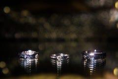 Tre fedi nuziali sulla superficie riflettente con i punti culminanti Fotografie Stock Libere da Diritti