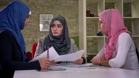 Tre femmine arabe del hijab grazioso stanno indicando alle carte e stanno parlando in ambiente di lavoro, mentre si sedevano nel  stock footage