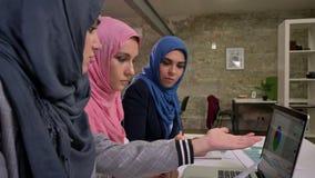 Tre femmine arabe del hijab piacevole stanno sedendo nella linea vicino al desktop comune e stanno indicando in computer portatil archivi video