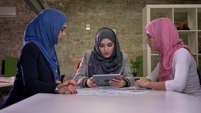 Tre femmine arabe del hijab stanno sedendo al desktop e stanno discutendo alcune edizioni di lavoro, mentre tenevano la compressa stock footage